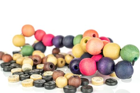 Lot of whole colorful wooden bead heap isolated on white wood