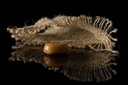 One whole caramel brown candy with jute fabric isolated on black glass