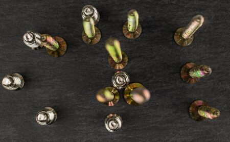 Group of fifteen whole metallic glossy bolt flatlay on grey stone Banco de Imagens - 131149642