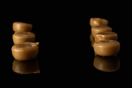 Lot of whole caramel brown candy in row isolated on black glass
