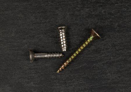 Group of three whole metallic glossy bolt flatlay on grey stone