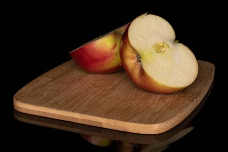 Group of two halves of red apple jonagold on bamboo cutting board isolated on black glass