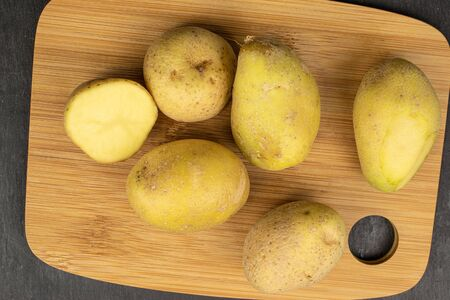 Group of five whole one half of raw brown potato on bamboo cutting board flatlay on grey stone