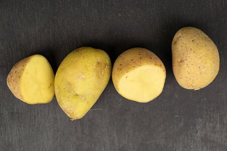 Group of two whole two halves of raw brown potato flatlay on grey stone 写真素材