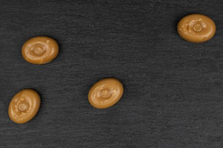 Group of four whole caramel brown candy flatlay on grey stone Stock Photo