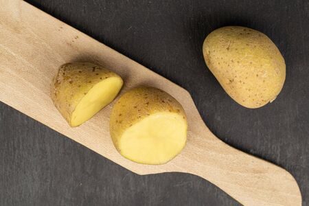 Group of one whole two halves of raw brown potato on  wooden board flatlay on grey stone