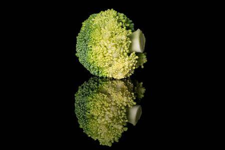 Whole fresh green broccoli isolated on black glass Stockfoto