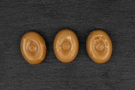 Group of three whole caramel brown candy flatlay on grey stone Stock Photo