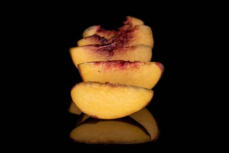 Group of five slices of sweet red peach isolated on black glass