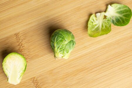 Group of one whole one half two pieces of fresh green brussels sprout flatlay on light wood