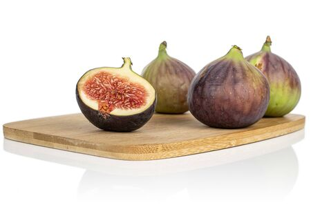 Group of three whole one half of sweet purple fig on bamboo cutting board isolated on white background