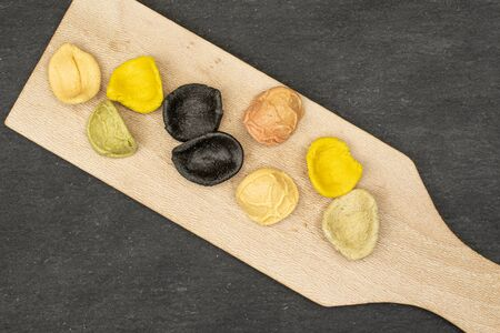 Group of nine whole colorful pasta orecchiette on wooden cutting board flatlay on grey stone