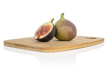 Group of one whole one half of sweet purple fig on bamboo cutting board isolated on white background Reklamní fotografie