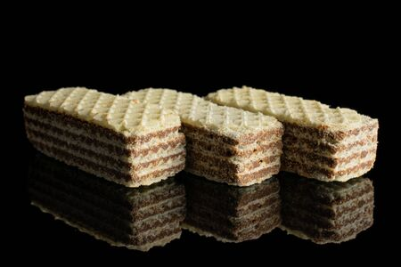 Group of three whole crispy beige hazelnut wafer cookie isolated on black glass 写真素材