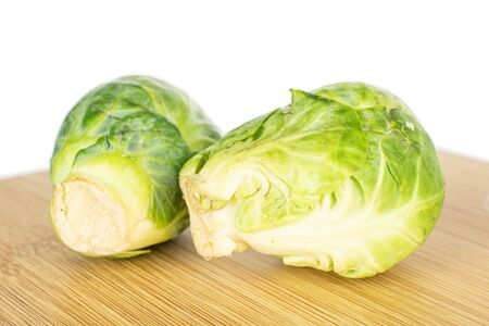 Group of two whole fresh green brussels sprout on bamboo cutting board isolated on white background 版權商用圖片