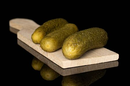 Group of three whole arranged sour green pickle on wooden cutting board isolated on black glass