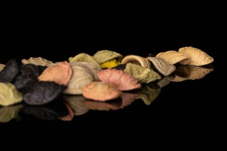 Lot of whole colorful pasta orecchiette heap isolated on black glass