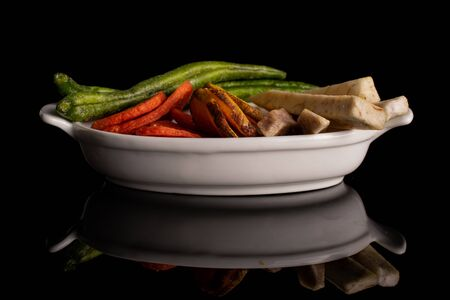 Lot of whole dry vegetable chip in white oval ceramic bowl isolated on black glass 写真素材