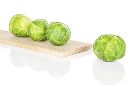 Group of four whole fresh green brussels sprout on wooden cutting board isolated on white background 版權商用圖片