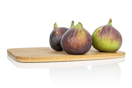 Group of four whole sweet purple fig on bamboo cutting board isolated on white background Reklamní fotografie