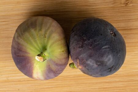 Group of two whole sweet purple fig flatlay on light wood Reklamní fotografie