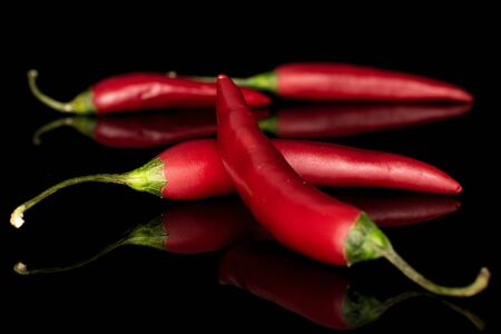 Group of four whole hot red chili cayenne crossed isolated on black glass Stock Photo