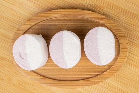 Group of three whole sweet pastel marshmallow on round bamboo coaster flatlay on light wood