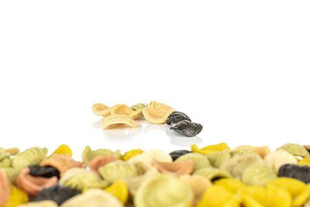 Lot of whole arranged colorful pasta orecchiette back focus isolated on white background Banco de Imagens