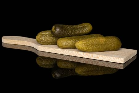 Group of four whole sour green pickle on wooden cutting board isolated on black glass