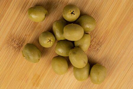Group of thirteen whole marinated green olive flatlay on light wood