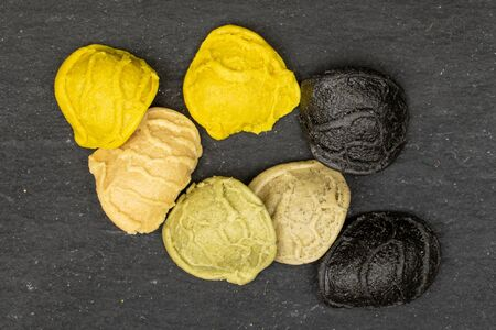 Group of seven whole colorful pasta orecchiette flatlay on grey stone