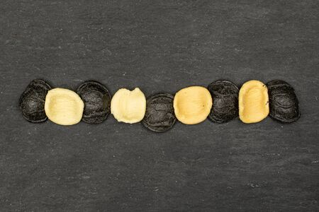Group of nine whole colorful pasta orecchiette flatlay on grey stone