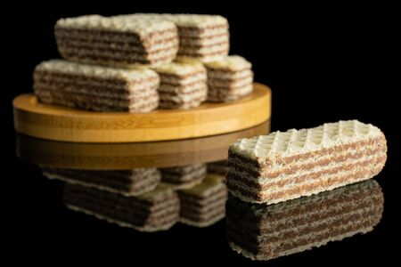 Group of six whole crispy beige hazelnut wafer cookie on bamboo coaster isolated on black glass 写真素材 - 131947264