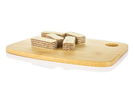 Group of five whole crispy beige hazelnut wafer cookie on bamboo cutting board isolated on white background