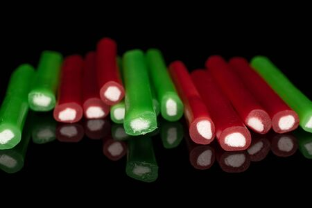 Lot of whole sweet stick candy in row isolated on black glass Banque d'images