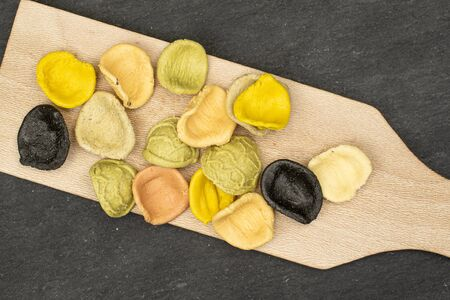 Lot of whole colorful pasta orecchiette on wooden cutting board flatlay on grey stone 版權商用圖片