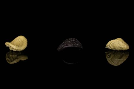 Group of three whole colorful pasta orecchiette isolated on black glass