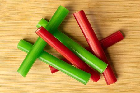 Group of six whole sweet stick candy flatlay on light wood