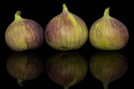 Group of three whole sweet purple fig isolated on black glass