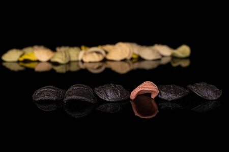 Lot of whole colorful pasta orecchiette in row isolated on black glass