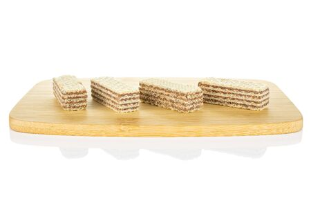 Group of four whole crispy beige hazelnut wafer cookie on bamboo cutting board isolated on white background 写真素材