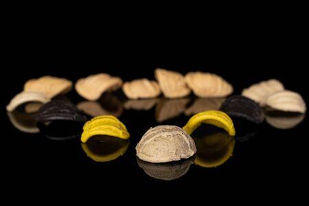 Lot of whole colorful pasta orecchiette isolated on black glass Reklamní fotografie