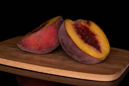 Group of two halves of sweet red peach on bamboo cutting board isolated on black glass