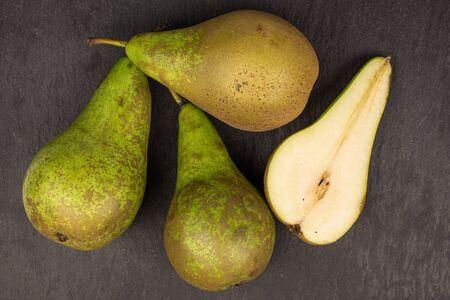Group of three whole one half of fresh green pear flatlay on grey stone