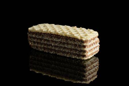 One whole crispy beige hazelnut wafer cookie isolated on black glass