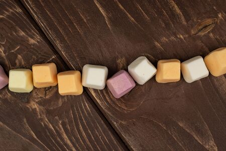 Lot of whole soft pastel candy flatlay on brown wood 스톡 콘텐츠