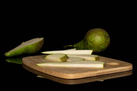Group of one whole one half five slices of fresh green pear on bamboo cutting board isolated on black glass