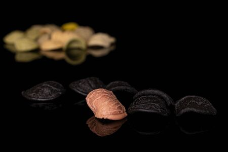 Lot of whole arranged colorful pasta orecchiette isolated on black glass