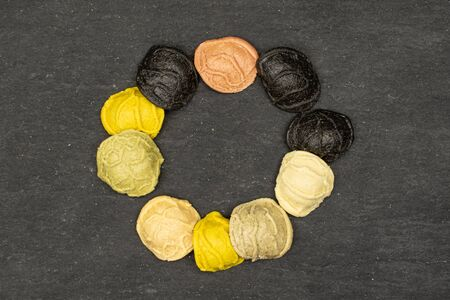 Group of ten whole colorful pasta orecchiette ring flatlay on grey stone