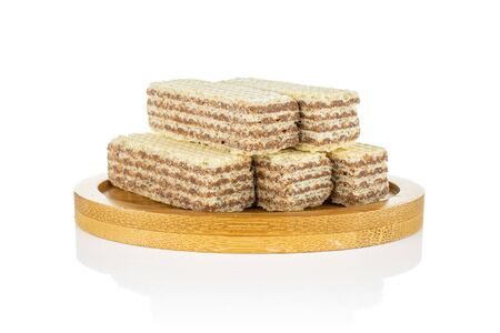 Group of five whole crispy beige hazelnut wafer cookie on bamboo coaster isolated on white background
